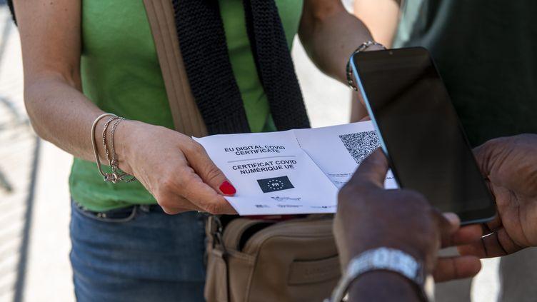 Une personne présente son pass sanitaire, le 21 juillet 2021 à Dijon. (EMMA BUONCRISTIANI / MAXPPP)