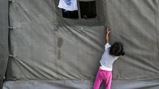 """Une enfant joue autour d""""une tente dans un centre de réfugiés à Presevo, le 25 août 2015. Au moins 2000 journée ont traversé la Serbie pendant pendant la journée du 25 août 2015 pour gagner la Hongrie, porte d'entrée dans l'Union européenne. Plus de 9000 migrants, pour la plupart des réfugiés Syriens, sont arrivés en Serbie en trois jours. (ARMEND NIMANI / AFP)"""