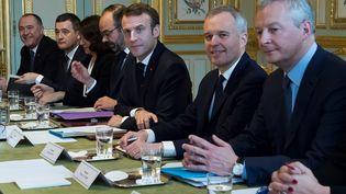 Le président de la République Emmanuel Macron, entouré du Premier ministre Edouard Philippe, du ministre de l'Ecologie François de Rugy et du ministre de l'Economie Bruno Le Maire, lors d'une réunion pour présenter un plan énergétique décennal pour la transition écologique, le 27 novembre 2018 à Paris. (IAN LANGSDON / POOL / AFP)