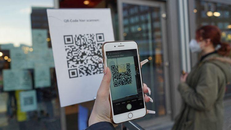 Un téléphone scanne un QR code à l'entrée d'un magasin de Berlin (Allemagne), le 9 mars 2021. (JORG CARSTENSEN / AFP)
