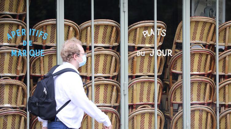 Un homme passe devant un restaurant fermé en raison de la pandémie de Covid-19, le 9 mai 2020 à Paris. (MAXPPP)