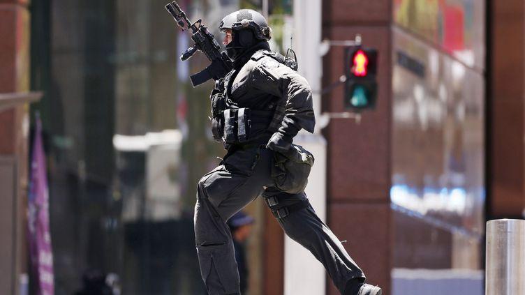 Un officier de police court prèsdu café Lindt de Sydney (Australie) où se tient une prise d'otage, le 15 décembre 2014. (DAVID GRAY / REUTERS)
