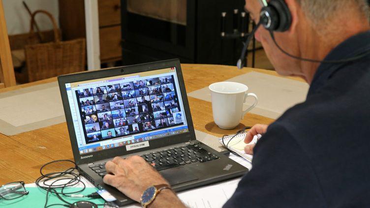 Un homme en télétravail sur la table du salon participe à une vidéoconférence, le 6 mai 2021. (VANESSA MEYER / MAXPPP)
