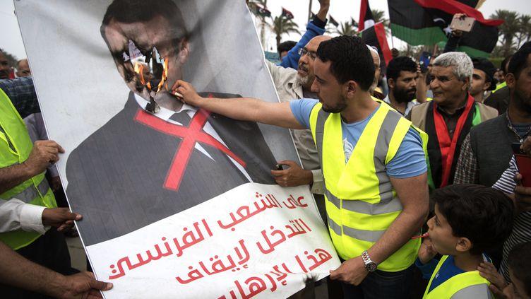 Des manifestants Lybiens brûlent une affiche d'Emmanuel Macron lors d'un rassemblement contre le maréchal Khalifa Haftar, à Tripoli. (FADEL SENNA / AFP)