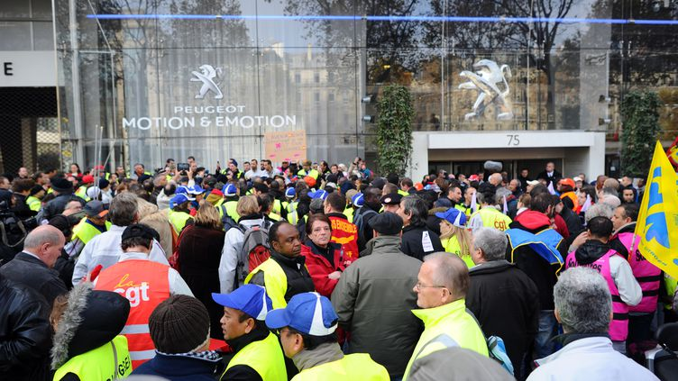 Des employés de PSA Peugeot Citroën manifestent devant le siège du groupe, le 15 novembre 2011, à Paris (MARTIN BUREAU / AFP)