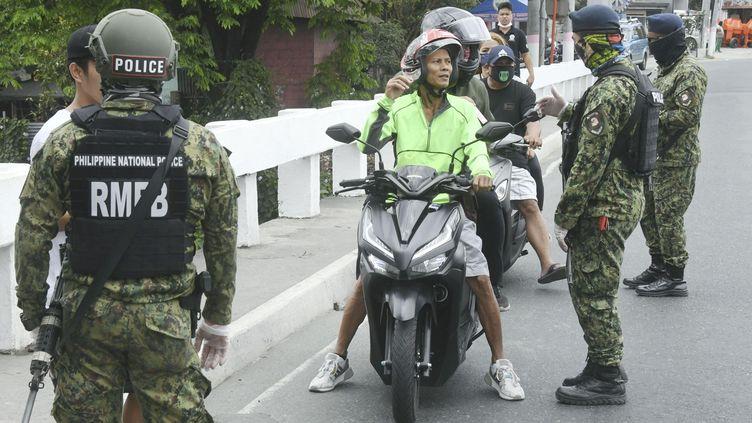 Des officiers de police armés arrêtent un motard à un checkpoint à Manille, le 15 mars 2020. (MAXPPP)