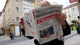 """Un homme lit le journal """"L'Humanité"""" à Thionville (Moselle), le 25 mai 2016. (MAXPPP)"""