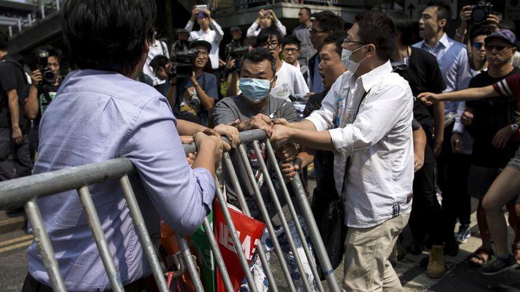 Des hommes masqués tentent de démanteler des barricades érigées par les manifestants pro-démocratie à Hong Kong, le 13 octobre 2014. (TYRONE SIU / REUTERS)