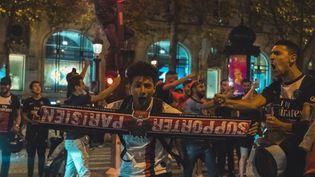 Des supporters du PSG fêtent la qualification du club pour la finale de la Ligue des champions sur les Champs-Elysées à Paris, le 18 août 2020. (BENJAMIN GUILLOT-MOUEIX / AFP)