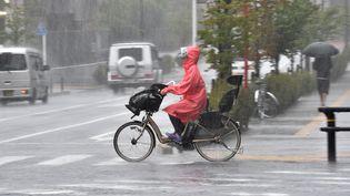 Une cycliste à Tokyo (Japon), lors du passage du typhon Phanfone, le 6 octobre 2014. (YOSHIKAZU TSUNO / AFP)