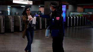 Un policier tend un masque à une passante à la gare d'Atocha, à Madrid (Espagne), le 13 avril 2020. (JAVIER SORIANO / AFP)