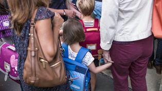 Devant une école primaire de Paris, lors de la rentrée 2015/2016, le 1er septembre 2015. (FRED DUFOUR / AFP)