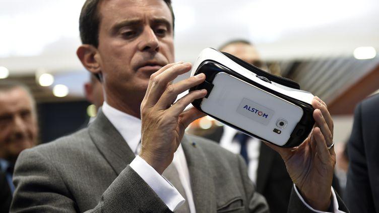 Manuel Valls examine des lunettes de réalité virtuelle montrant un nouveau modèle de train Alstom, le 1er octobre 2015, à Chassieu (Rhône). (PHILIPPE DESMAZES / AFP)
