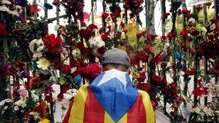 Un sympathisant de l'indépendance catalane dépose une fleur devant un bureau de vote utilisé lors du référendum d'autodétermination, mardi 3 octobre 2017 à Barcelone. (PAU BARRENA / AFP)
