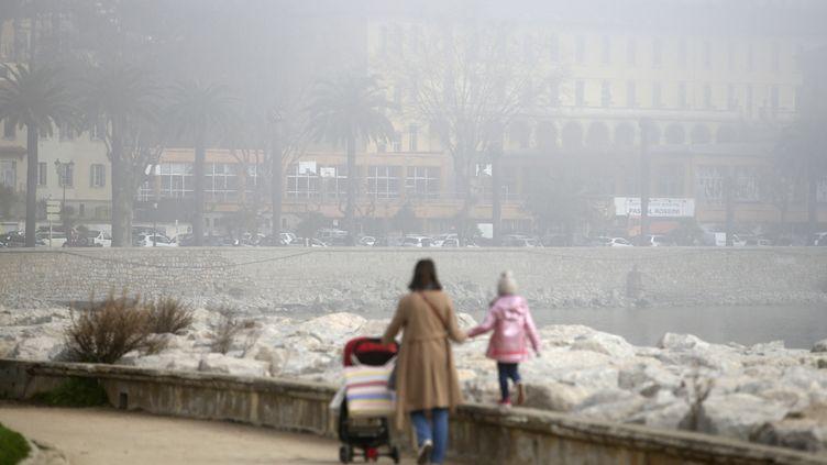 Une femme et ses enfants marchent dans une rue d'Ajaccio alors qu'un nuage de pollution enveloppe la ville, le 25 février 2021. (PASCAL POCHARD-CASABIANCA / AFP)