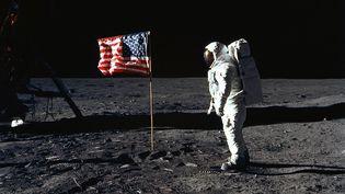 L'astronaute Buzz Aldrin prend la pose sur la Lune à côté du drapeau américain, devant l'objectif de Neil Armstrong. (AFP PHOTO / NASA / NEIL ARMSTRONG)