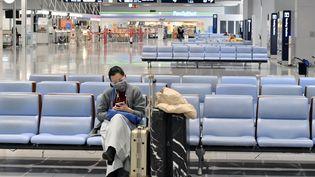 Une voyageuse patiente, seule, dans l'aéroport international du Kansai, à Osaka (Japon), le 7 avril 2020. (NAOYA AZUMA / YOMIURI / AFP)