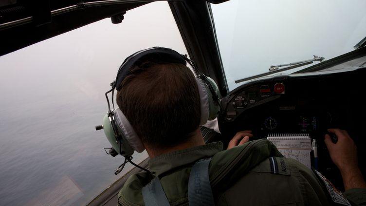 Un officier australien survole l'océan Indien, le 24 mars 2014, à la recherche de débris du Boeing disparu de la Malaysia Airlines. (RICHARD WAINWRIGHT / AFP)