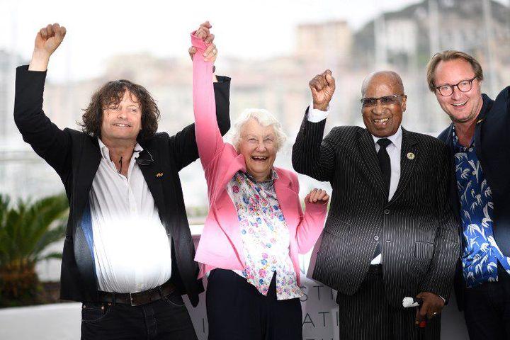 Andrew Mlangeni, bras levé, avec les réalisateurs du documentaire «L'Etat contre Mandela et les autres». (LOIC VENANCE / AFP)