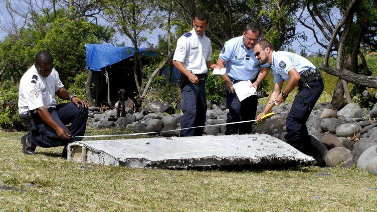 Des policiers inspectent un débris du vol MH370 retrouvé à La Réunion, le 29 juillet 2015. (MAXPPP)