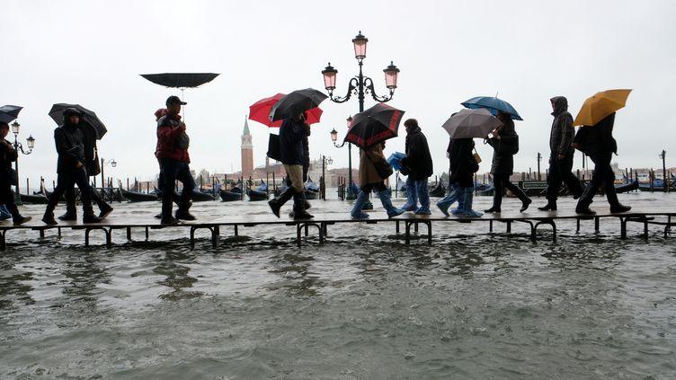Des personnes traversent la place Saint-Marc, le 12 novembre 2019 à Venise (Italie). (MANUEL SILVESTRI / REUTERS)