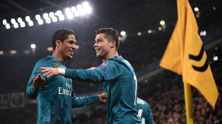 Réunis sous le même maillot du Real Madrid, Raphaël Varane et Cristiano Ronaldo célèbrent un but lors du match aller des quarts de finale de la Ligue des Champions 2018 contre la Juventus, futur club du Portugais. (MARCO BERTORELLO / AFP)
