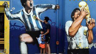 Un homme et son fils rendent hommage à Diego Maradona devant une peinture murale qui représente le footballeur à Buenos Aires, en Argentine. (ALEJANDRO PAGNI / AFP)