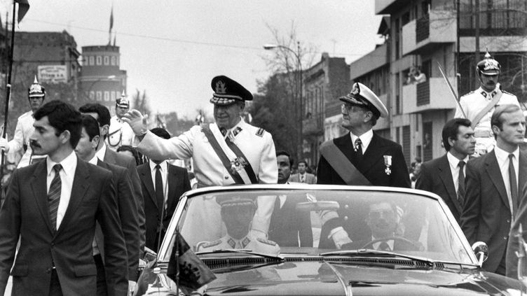 Le général Augusto Pinochet, chef de la junte militaire chilienne, salue le cortège du 11 septembre 1973 à Santiago peu de temps après son coup d'État, le 11 septembre 1973. (AFP)
