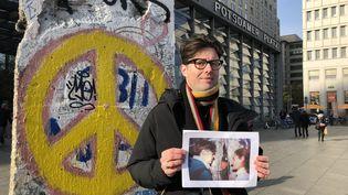 Éric Giriat, à l'endroit où il a rencontréle policier est-allemand avec la photo souvenir du 11 novembre 1989. Sur cette image, au centre, le policier est-allemand, de l'autre côté du mur. (LUDOVIC PIEDTENU / RADIO FRANCE)