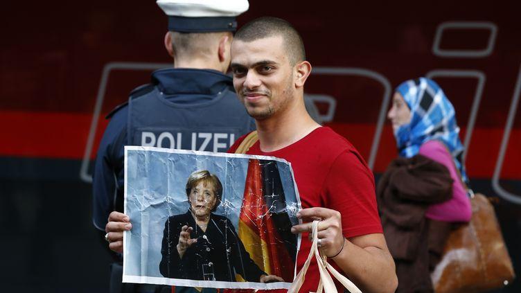 Un migrant brandit une photo de la chancelière allemande Angela Merkel à son arrivée en gare de Munich (Allemagne), le 5 septembre 2015. (MICHAEL DALDER / REUTERS)