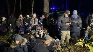 Des migrants irakiens attendent l'arrivée de l'officier des gardes-frontières polonais qui va décider deleurmise en détention provisoire en Pologne, dans les environs de Hajnowka, le 21 octobre 2021. (FABIEN MAGNENOU / FRANCEINFO)