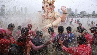 Pour demander au dieu éléphant de leur apporter la prospérité, des Hindous plongent une statue de Ganesh dans la mer d'Arabie à Bombay (Inde), le 8 septembre 2014. (DANISH SIDDIQUI / REUTERS)