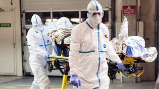 Des soignants transportent une personne infectée par Ebola de la Sierra Leone à Genève (Suisse), le 21 novembre 2014. (GENEVA UNIVERSITY HOSPITAL (HUG) / AFP)