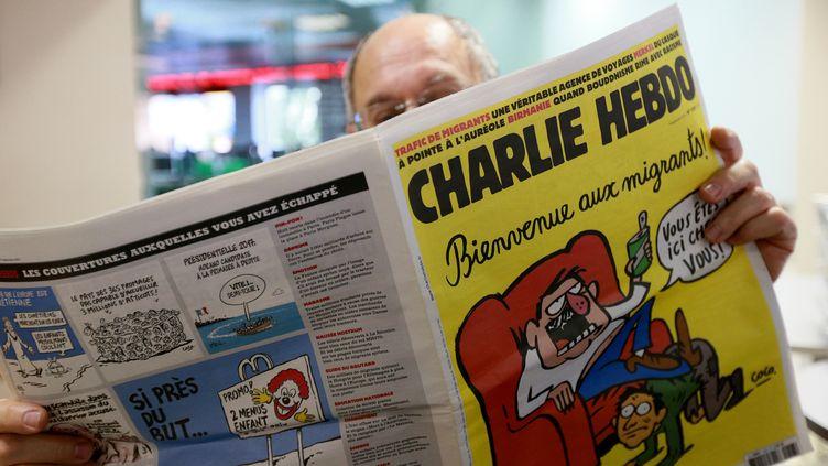 """Un homme lit le numéro de """"Charlie Hebdo"""" paru le 18 septembre 2015. (ANTON DENISOV / RIA NOVOSTI / AFP)"""
