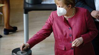 Angela Merkel glisse son bulletin dans l'urne lors du vote de la loi permettant la mise en place d'un couvre-feu national contre le Covid-19 au Bundestag, à Berlin, mercredi 21 avril 2021. (KAY NIETFELD / DPA)