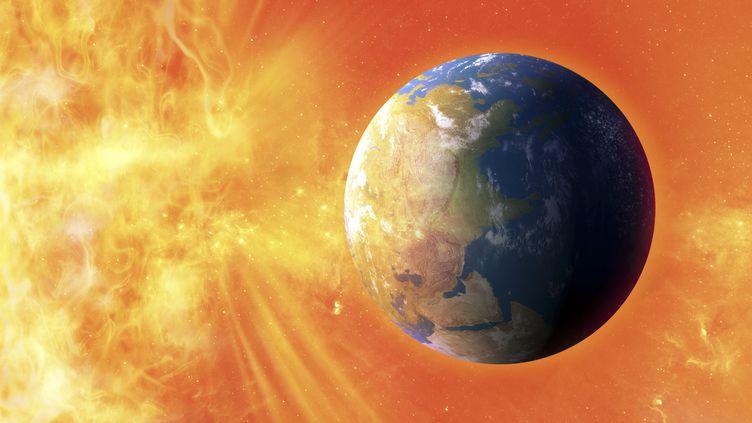 Vue d'artiste montrant d'une éruption solaire frappant la Terre. (VHB / SCIENCE PHOTO LIBRARY / AFP)