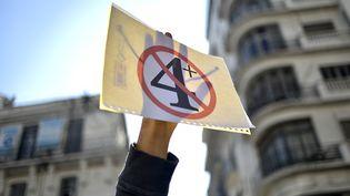 Un étudiant brandit une pancarte dans une manifestation contre la prolongation du mandat d'Abdelaziz Bouteflika, à Alger (Algérie), le 12 mars 2019. (RYAD KRAMDI / AFP)