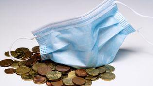Image d'illustration montrant un masque chirurgical avec des pièces de monnaie. (JOEL SAGET / AFP)
