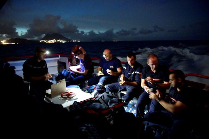 Des pompiers français à bord d'un bateau se dirigeant vers l'île de Saint-Martin depuis la Guadeloupe, le 8 septembre 2017, après le passage de l'ouragan Irma. (MARTIN BUREAU / AFP)