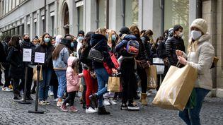 Des personnes masquées font la queue devant un magasin à Genève, en Suisse, le 16 janvier 2021. (FABRICE COFFRINI / AFP)