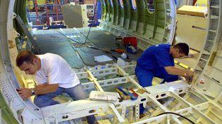Deux ouvriers de l'usine aéronautique Latécoère de Toulouse travaillent le 5 juillet 2002 sur la fabrication d'une structure d'avion Airbus. (PASCAL PAVANI / AFP)