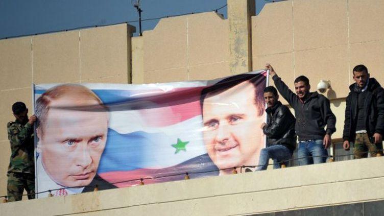 Des étudiants de l'université al-Bath de Homs brandissent une banderole aux effigies de Vladimir Poutine et Bachar al-Assad, le 18 novembre 2015, en soutien à l'intervention de la Russie en Syrie. (Dmitriy Vinogradov/RIA Novosti/AFP)