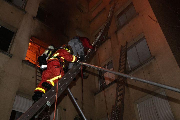 Un sapeur-pompier secourt un sinistré pendant l'incendie d'un immeuble rue Erlanger à Paris, le 5 février 2019. (BENOIT MOSER / BRIGADE DE SAPEURS-POMPIERS DE PARIS)
