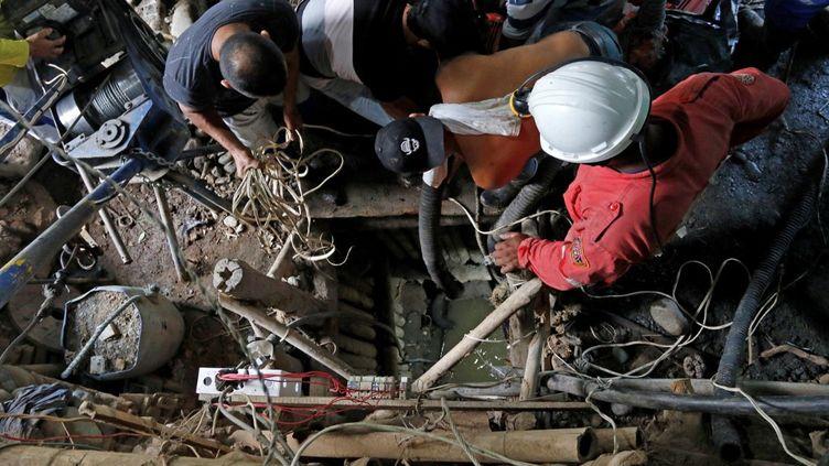 Des pompiers et des secouristes recherchent des mineurs coincés dans une mine d'or à Neira (Colombie), le 27 mars 2021. (JOHN BONILLA / AFP)