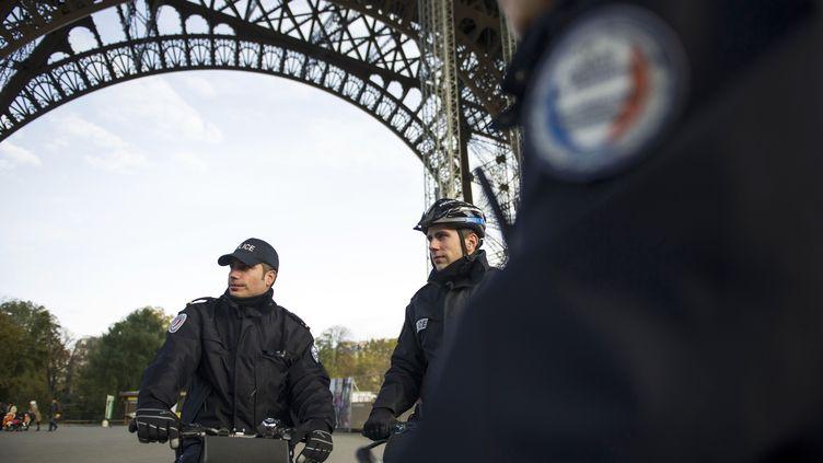 Des policiers patrouillent sous la tour Eiffel, le 19 novembre 2013, à Paris. (FRED DUFOUR / AFP)