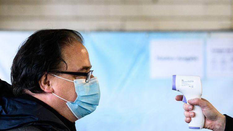 Un homme se fait prendre la température par un thermomètre sans contact, le 2 décembre 2020 à Mayence (Allemagne). (ANDREAS ARNOLD / DPA)