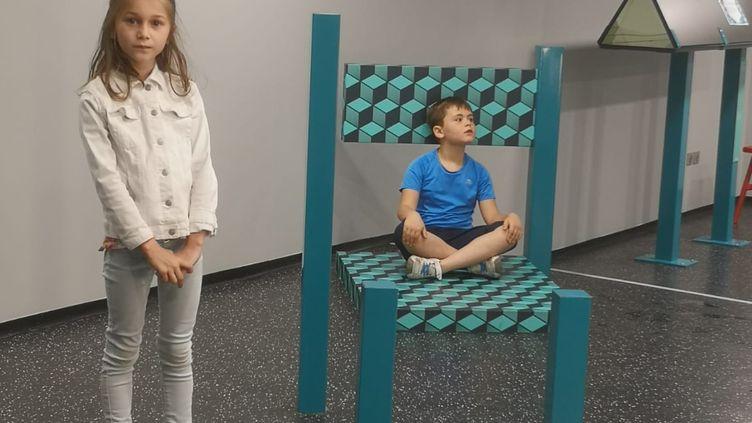 Terry et Sonam testent la chaise BEUCHET au Musée de l'Illusion, à Paris. (G.CAUZOT)