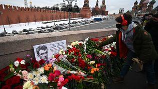 Une femme dépose des fleurs sur le pont où a été assassiné Boris Netmsov en 2015. (EVGENY ODINOKOV / SPUTNIK / AFP)