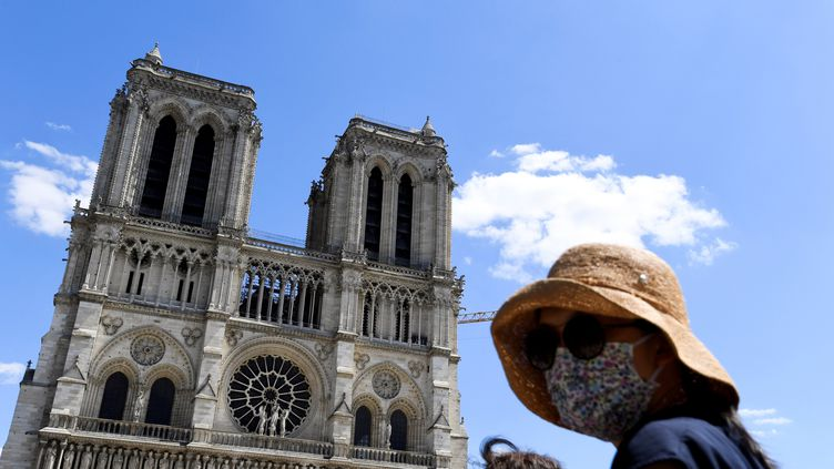 Une femme portant un masque se tient sur le parvis de Notre-Dame, le 31 mai 2020. (ALAIN JOCARD / AFP)
