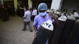 Un soignant transporte une bouteille d'oxygène àAllahabad en Inde, le 20 avril 2021. Les hôpitaux sont confrontés à une pénurie d'oxygène. (SANJAY KANOJIA / AFP)